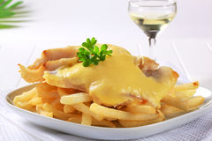 Cheese topped fish fillets with French fries Stock Photography