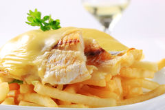 Cheese topped fish fillets with French fries Stock Photos