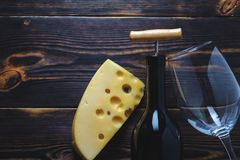 Cheese two bottles of wine and a glass of wooden background space for copy royalty free stock photography