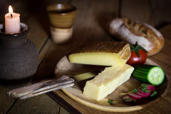 Cheese and vegetables with candlelight on a wooden table Stock Image