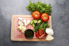 Cheese and vegetables served on wooden plate Stock Images