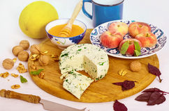 Cheese, walnut and peaches on the wooden board. With melon and honey Royalty Free Stock Photo