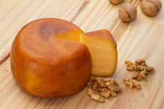 Cheese wheel and slice with nuts Stock Photos