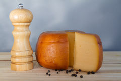 Cheese wheel and slice with wooden peppermill with peppercorns Stock Photo