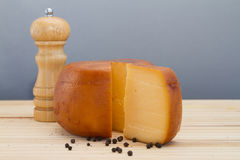 Cheese wheel and slice with wooden peppermill with peppercorns Stock Images