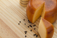 Cheese wheel and slice with wooden peppermill with peppercorns Royalty Free Stock Photography