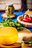 Cheese wheel on a wooden board. Blurred background royalty free stock image