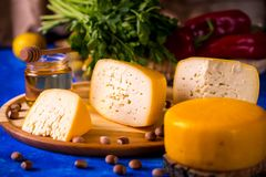 Cheese wheel on a wooden board. Blurred background stock image