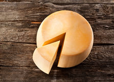 Cheese wheel on wooden table Royalty Free Stock Photography