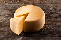 Cheese wheel on wooden table Royalty Free Stock Photos