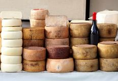 Cheese wheels of Pecorino and Sardinian ricotta in different stacks on a shelf of an outdoor market. A bottle of red wine Cannonau in the middle royalty free stock photos