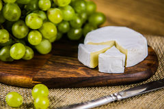 Cheese with white grape on a wooden board Royalty Free Stock Photography