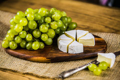 Cheese with white grape on a wooden board Stock Photography