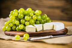 Cheese with white grape on a wooden board Stock Image