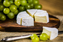 Cheese with white grape on a wooden board Royalty Free Stock Photos