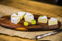 Cheese with white grape on a wooden board Stock Images