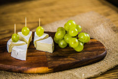 Cheese with white grape on a wooden board Royalty Free Stock Images