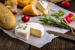 Cheese with white mold, radish, grapes and baguette with herbs Stock Photography