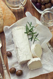 Cheese on white paper, glass of white wine Stock Image