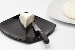 Cheese on a white plate with a portion cut in an other black plate Royalty Free Stock Photo
