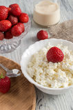 Cheese in white plate with strawberries on a wooden table with canvas tablecloth. Royalty Free Stock Photo