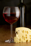 Cheese and wine. Piece of cheese close-up, glass of red wine and wine bottle on brown wood surface Stock Photo