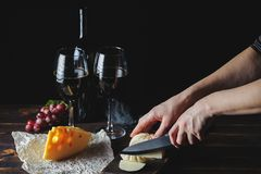 Cheese wine and bunches of grapes on a black background stock images