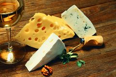 Cheese and wine in a glass on a wooden board. stock photos