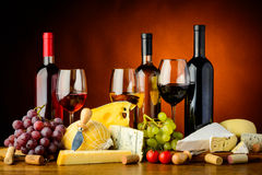 Cheese, wine and grapes. Still life with cheese, grapes, red, white and rose wine Stock Image