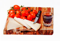 Cheese, wine and tomatoes. Cutting Board with sheep cheese, wine and tomatoes Stock Photos