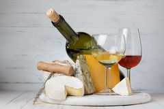 Cheese and wine on wooden table Stock Images