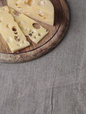 Cheese on the wood plank on the linen canvas Royalty Free Stock Images