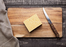 Cheese on wooden kitchen board with knife Royalty Free Stock Photo