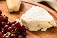 Cheese on wooden plate with grapes Royalty Free Stock Images