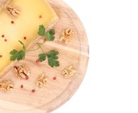 Cheese on wooden platter with walnuts. Royalty Free Stock Image