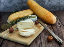 Cheese on a wooden table with olives and bread stock photography