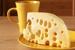 Cheese and yellow cup. Piece of cheese close-up on yellow plate and yellow cup on beige wood surface Stock Image