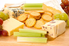 Cheeseboard. Close up of a variety of cheese and garnishes on a wooden cheeseboard Stock Photography