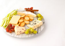 Cheeseboard. Selection of cheeses with biscuits and garnish on a marble cheeseboard Stock Photos