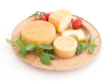 Cheeseboard with artisan cheeses and tomatoes, over white Royalty Free Stock Images