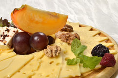 Cheeseboard: cheese and fruits. Cheese and some fruits on the wood plate Royalty Free Stock Image