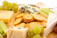 Cheeseboard Close-Up. Close up of a variety of cheese and garnishes on a wooden cheeseboard isolated against a white background Royalty Free Stock Images
