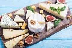 Cheeseboard con il parmigiano, il camembert e il dorblu del brie del formaggio Alimento sul bordo di legno fotografie stock libere da diritti
