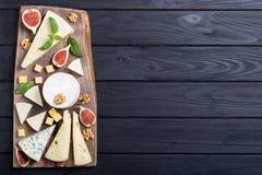 Cheeseboard con il parmigiano, il camembert e il dorblu del brie del formaggio Alimento sul bordo di legno immagine stock