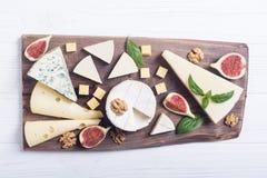 Cheeseboard con il parmigiano, il camembert e il dorblu del brie del formaggio Alimento sul bordo di legno fotografia stock