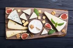 Cheeseboard con il parmigiano, il camembert e il dorblu del brie del formaggio Alimento sul bordo di legno immagini stock
