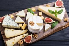 Cheeseboard con il parmigiano, il camembert e il dorblu del brie del formaggio Alimento sul bordo di legno fotografia stock libera da diritti