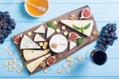 Cheeseboard con il parmigiano, il camembert e il dorblu del brie del formaggio Alimento sul bordo di legno immagini stock libere da diritti