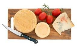 Cheeseboard con los tomates y el cuchillo Queso del artesano Aislado Foto de archivo libre de regalías