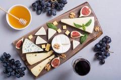 Cheeseboard con parmesano, camembert y dorblu del brie del queso Comida en el tablero de madera fotos de archivo